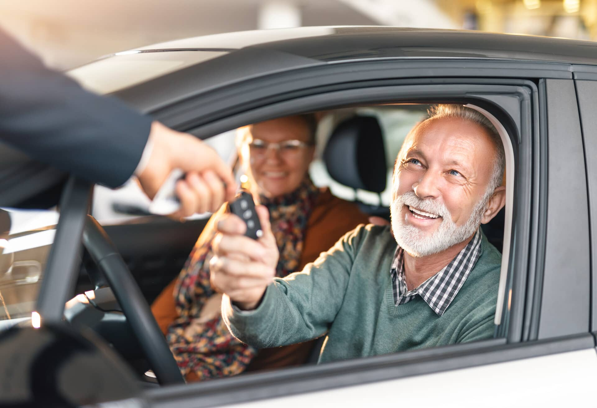 Ældre par, der kører i en lejebil.
