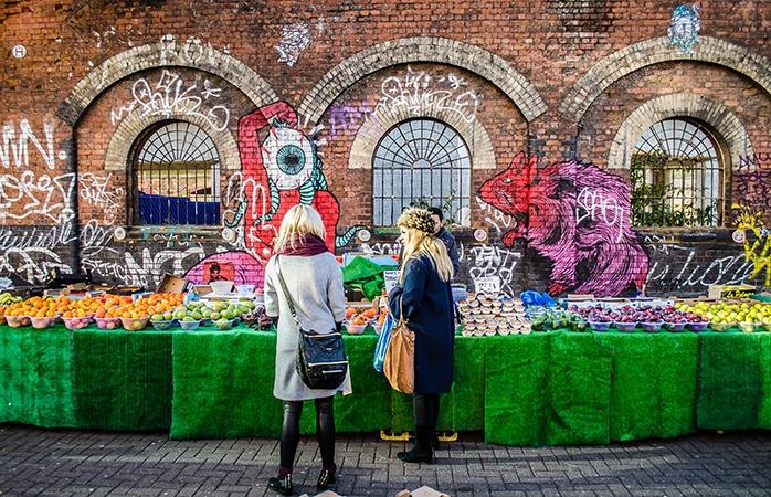 To unge piger ved en frugtbod nær Brick Lane, East London.